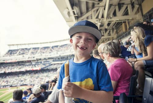 boy smiles as he eats a snack at a baseball game at coors field