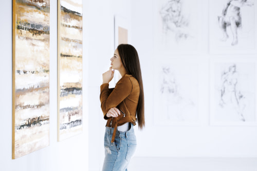 woman admires artwork at a museum