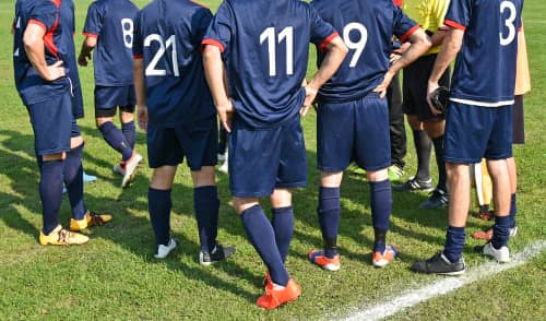 soccer team members huddle on the field