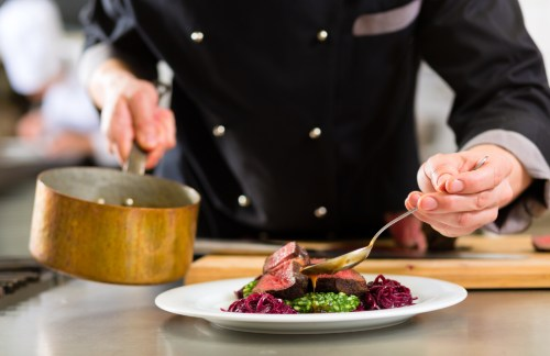 a professional chef plates a dish in a fine dining restaurant