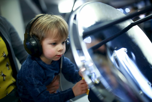 young boy looks at science exhibit at houston museum