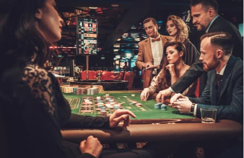 Group of well-dressed young people at a poker table