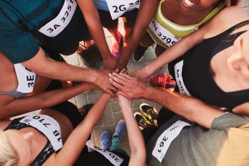 team members put their hands into a circle before a game