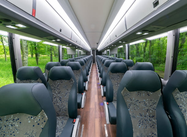 the interior seats of an MCI charter bus, with wood floors
