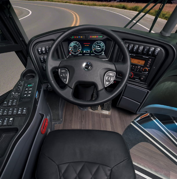 the interior driver's area of an mci charter bus, with a steering wheel and controls