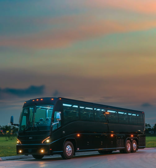 an mci j4500 charter bus driving at sunset