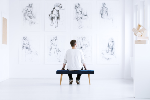 a man admires drawings in an art gallery