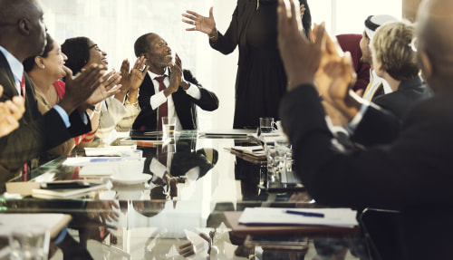 coworkers clap for leader during business meeting