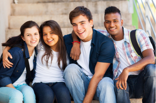 Group of diverse teenage students sitting together on steps