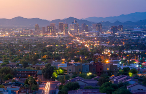 Skyline of Downtown Phoenix in the early dusk with mountains in background