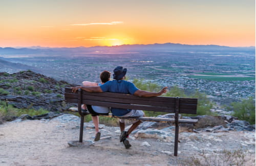 Couple sitting on a bench atop Dobbins Lookout at South Mountain Park overlooking Arizona landscape
