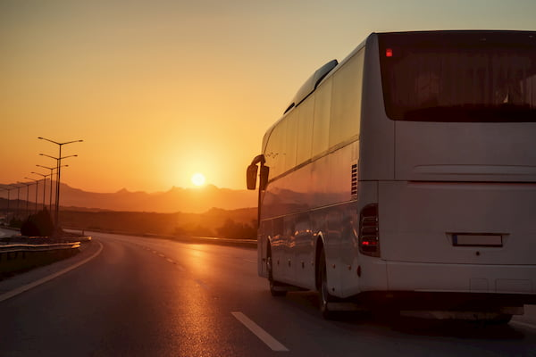 a bus drives on a long road into the sunset