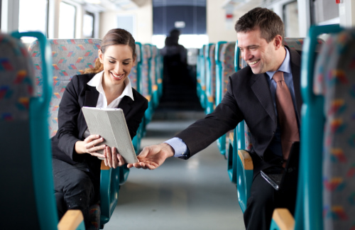 two business professionals look over a tablet device on a charter bus