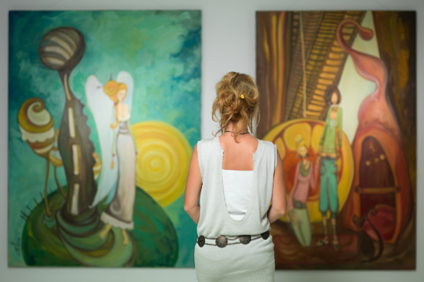 Woman admires two paintings in an art gallery