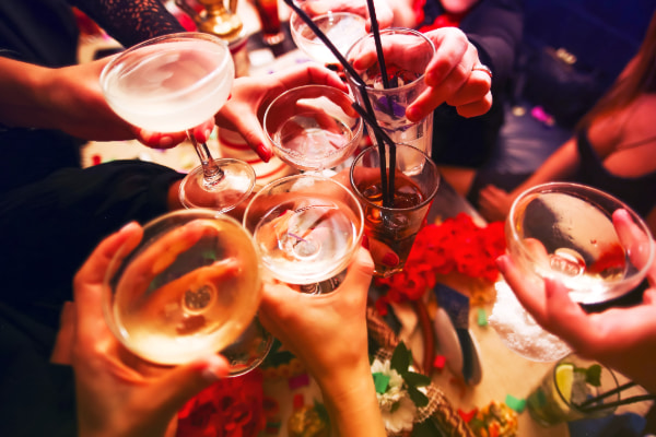 Friends toast aa variety of alcoholic drinks at a party
