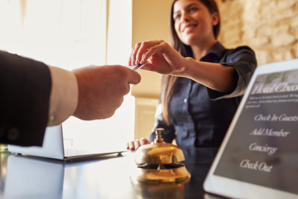 concierge hands a keycard to guest at a hotel front desk