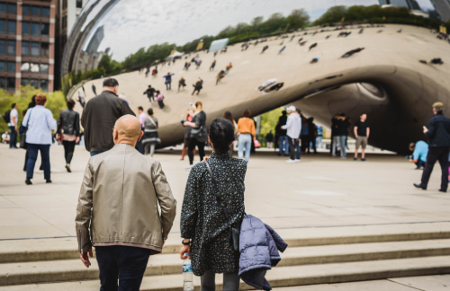 a couple stands admires Chicago's Cloud Gate sculpture from afar