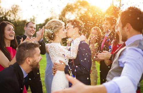 a bride and groom celebrate their outdoor wedding with friends