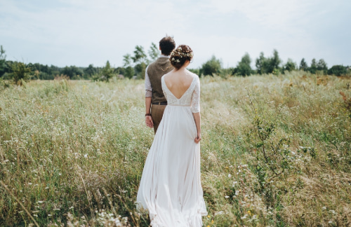 a bride and groom walk through a Texas field