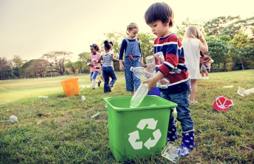 a group of child gather and recycle plastic bottles in a park