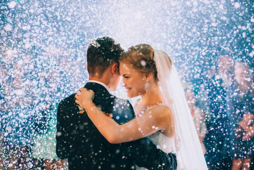 newlywed couple smiles while bubbles fill the background