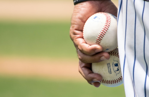 A professional baseball player holds two baseballs during a game