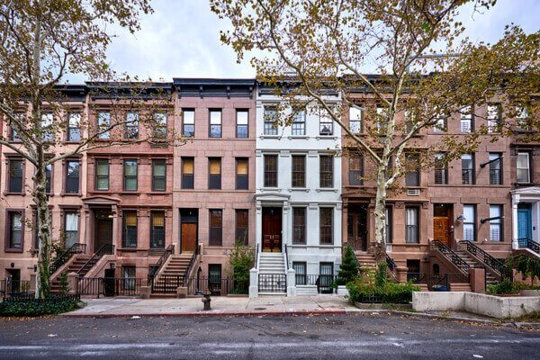 classic New York City brownstone buildings lined up on a city street
