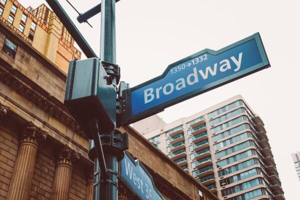 New York City street sign reading Broadway on a street corner