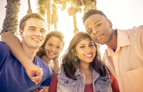 usc students pose for a picture in front of palm trees
