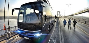 a blue temsa bus drives on a bridge