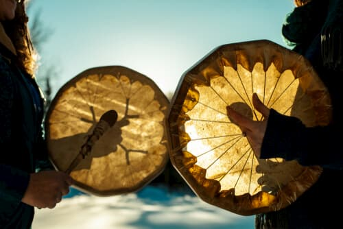Two people playing traditional Native American drums