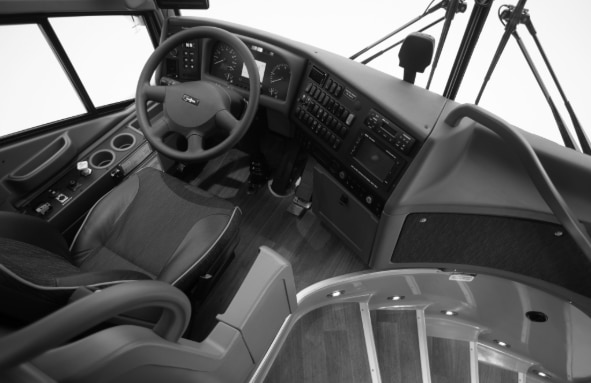 The interior of a Van Hool bus, including the controls and steering wheel