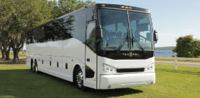 a white van hool charter bus parked on grass
