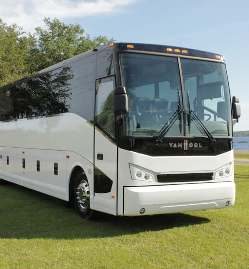 A white Van Hool charter bus parks in a grassy field