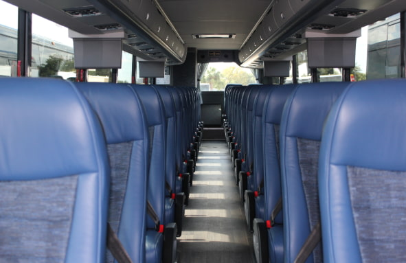 The passenger seats of a Van Hool charter bus, as viewed from the entrance