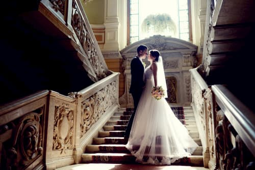 Bride and groom kissing on elegant staircase