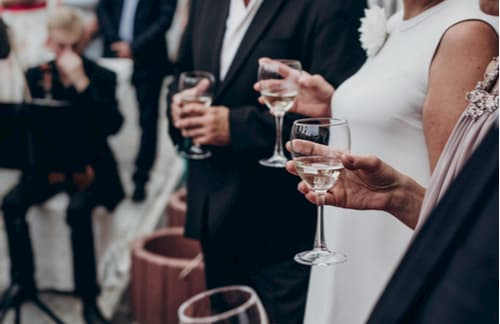 Wedding couple and guests holding wine