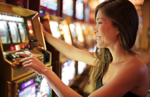 A woman smiles and tries her luck at a Las Vegas slot machine