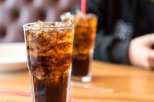 two glasses filled with coke
